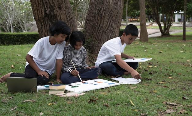 Tre bambini seduti sul prato verde al piano terra, dipingono il colore su tela, facendo attività insieme a sentimento felice, in un parco