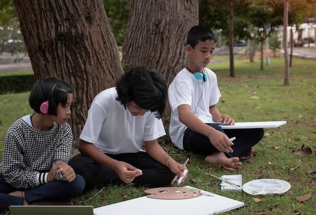 Tre bambini seduti sul pianterreno dell'erba verde, dipingono il colore su tela e parlano, facendo attività insieme alla sensazione di felicità, in un parco