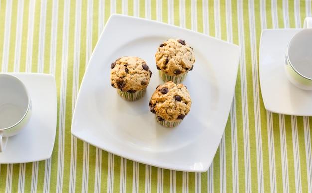 Tre muffin con gocce di cioccolato su un piatto bianco e una tovaglia a strisce verdi a colazione