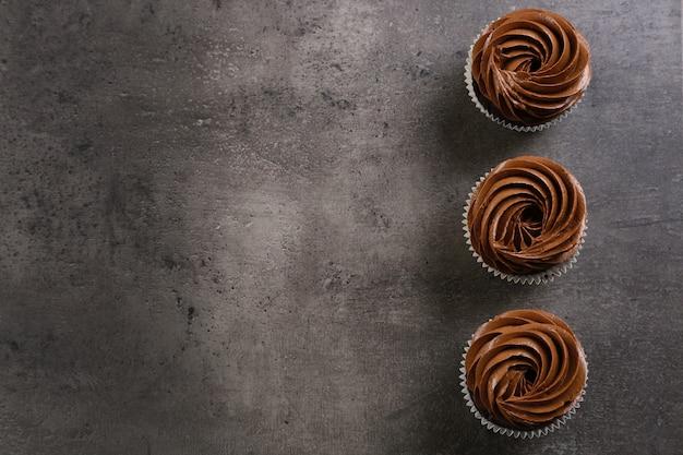 Tre cupcakes al cioccolato su grigio
