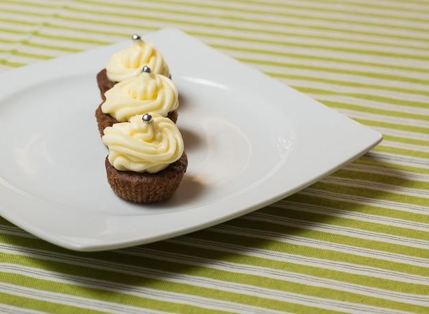 Tre cupcakes al cioccolato con granelli d'argento sulla parte superiore, su un piatto bianco e una tovaglia di tessuto a strisce