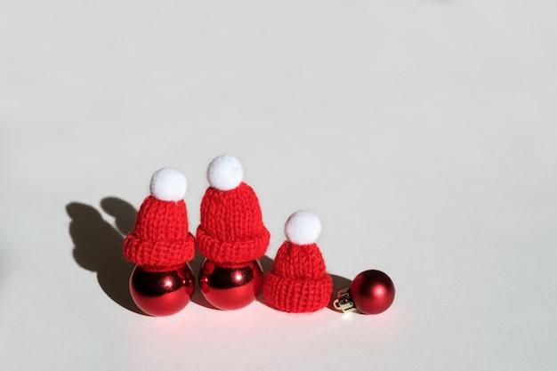 Tre palle di natale con cappelli a maglia rossi su sfondo bianco
