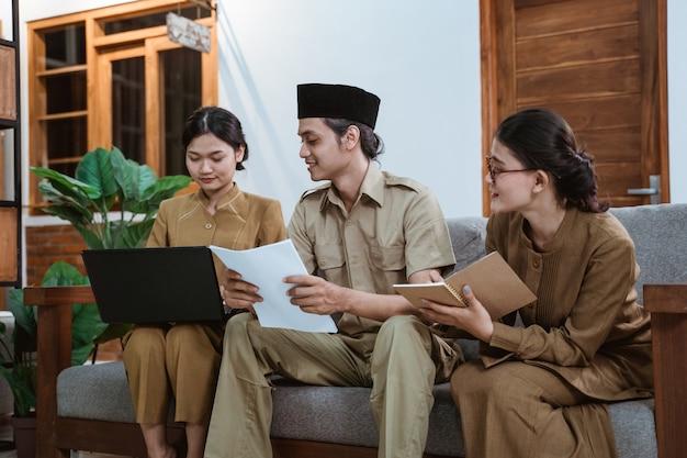 Tre dipendenti pubblici che lavorano da casa utilizzando fogli di lavoro e quaderni di computer portatili