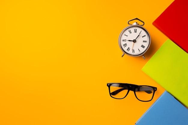 Tre taccuini con copertina rigida a colori e sveglia su sfondo giallo vista dall'alto