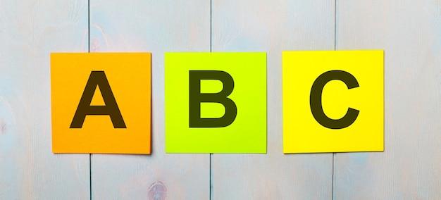 Tre adesivi colorati con la scritta abc su uno sfondo di legno azzurro