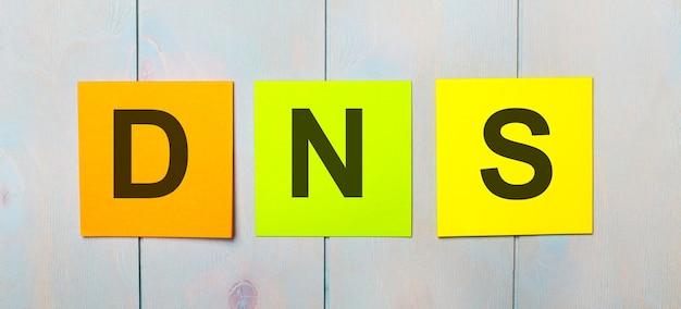 Tre adesivi colorati con il testo dns domain name system su uno sfondo di legno azzurro