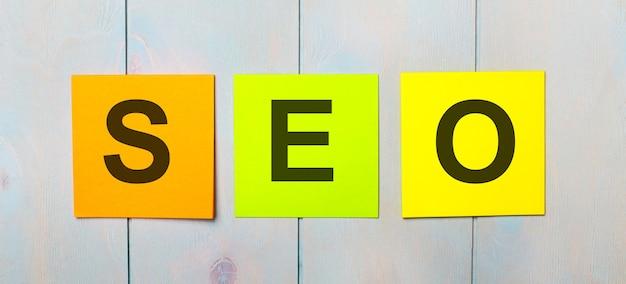 Tre adesivi colorati con il testo seo search engine optimization su una superficie di legno azzurra