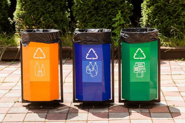 Tre bidoni della spazzatura colorati in un parco accanto a un sentiero.
