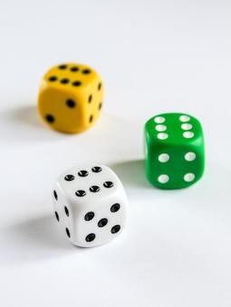 Tre dadi colorati isolati su superficie bianca