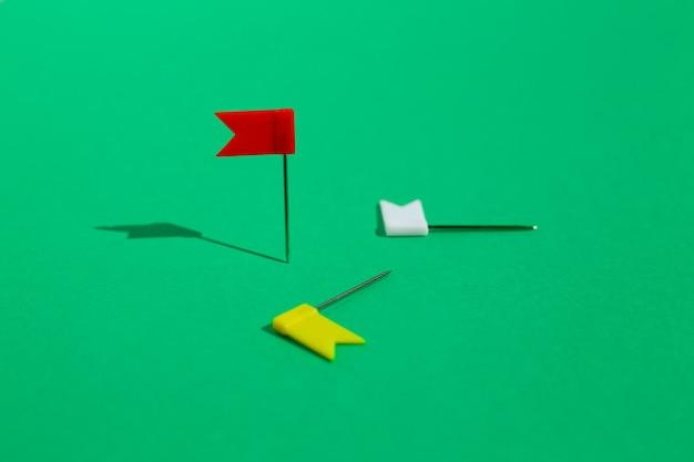 Tre piccoli perni colorati della bandiera appuntati su una superficie verde. business o concetto di viaggio. gli obiettivi .