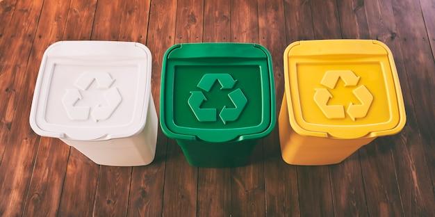 Tre bidoni della spazzatura colorati per lo smistamento dei rifiuti. per plastica, vetro e carta