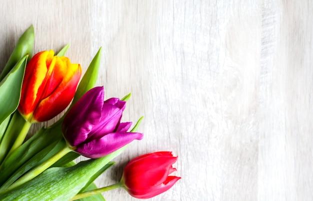 Tre tulipani colorati su fondo in legno. cartolina d'invito per la festa della mamma o la giornata internazionale della donna. fiore luminoso minimalista per pubblicità o promozione. fiori di primavera.