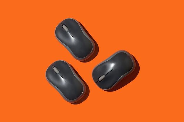 Tre mouse per computer su sfondo arancione