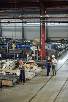 Tre professionisti contemporanei di caschi e abbigliamento da lavoro che svolgono il loro lavoro in uno dei laboratori di fabbrica