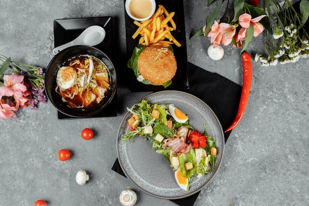 Pranzo di lavoro di tre portate. pranzo con hamburger di spaghetti ramen asiatici e insalata caesar.