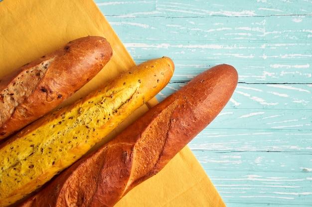 Tre baguette francesi croccanti giacciono baguette di fondo in legno blu in assortimento con semi di sesamo pasticcini nazionali francesi classici