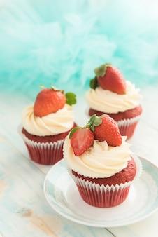 Tre cupcake di velluto rosso con un cappellino di crema di formaggio e fragole