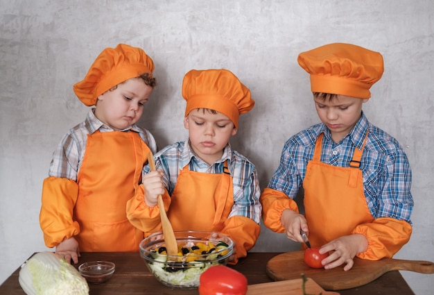 Tre simpatici ragazzi europei in costume arancione cucinano preparano un'insalata di verdure. cucinare una cena in famiglia