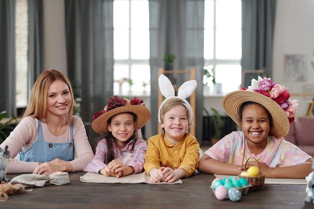 Tre bambini carini e una giovane donna bionda in abbigliamento casual che ti guardano con sorrisi a trentadue denti mentre sono seduti al tavolo davanti alla telecamera