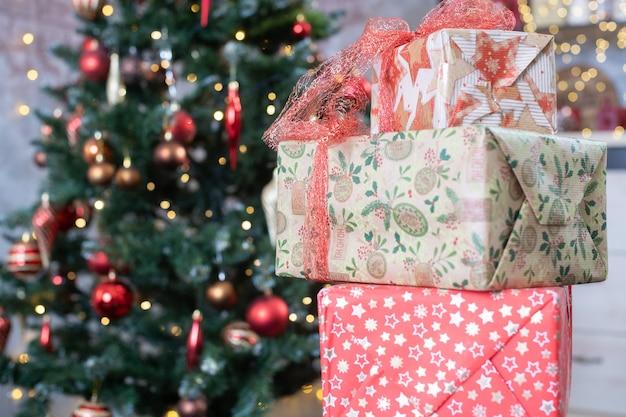 Tre scatole regalo decorate in carta artigianale con fiocchi per capodanno e vacanze di natale e abete con palla di giocattoli sui rami sullo sfondo