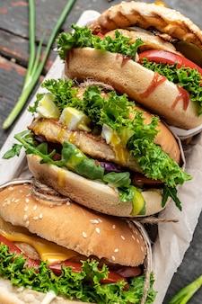 Tre deliziosi hamburger fatti in casa di manzo, formaggio e verdure, tentazione dietetica con conseguente nutrizione malsana. vista dall'alto