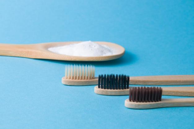 Tre diverse spazzole di bambù e un cucchiaio di legno con soda su una superficie blu