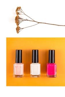 Tre diversi colori di smalto per unghie su una superficie calda e luminosa con un bouquet di fiori secchi Foto Premium