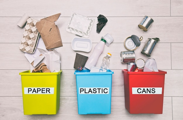 Tre diversi contenitori pieni per lo smistamento dei rifiuti. per plastica, carta, metallo