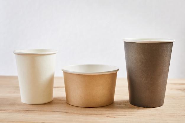 Tre tazze di caffè di carta differenti sulla tavola di legno, fine su