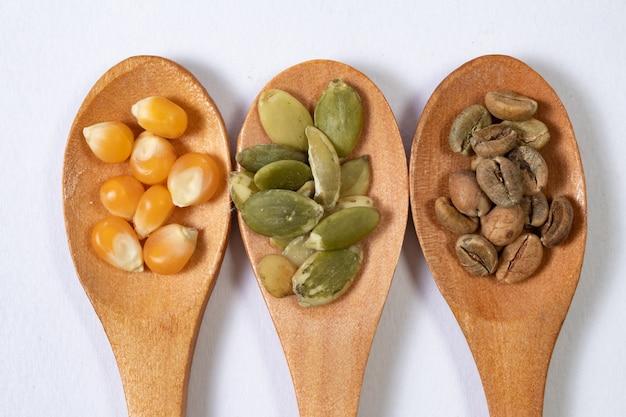 Tre diversi semi in cucchiai di legno su una superficie bianca