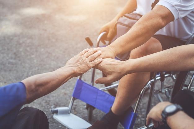 Tre delle persone disabili che si siedono sulla sedia a rotelle e che mettono insieme le mani
