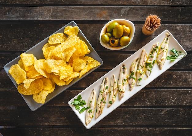 Tre piatti con patatine fritte, acciughe raccolte e olive verdi su un tavolo di legno scuro con stuzzicadenti. tipici spuntini spagnoli.