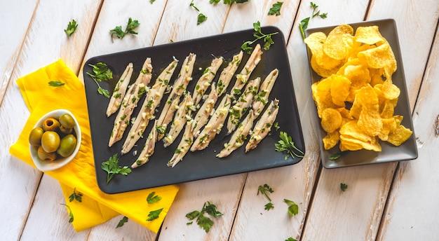 Tre piatti con patatine fritte, acciughe raccolte e olive verdi su un tavolo in legno bianco con foglie di prezzemolo. tipici spuntini spagnoli.