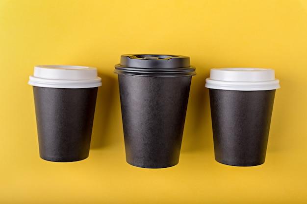 Tre tazze di carta usa e getta nere di diverse dimensioni per il caffè da asporto piatto giacevano su sfondo giallo