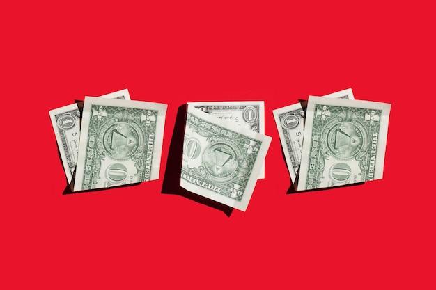 Tre banconote da un dollaro su uno sfondo rosso