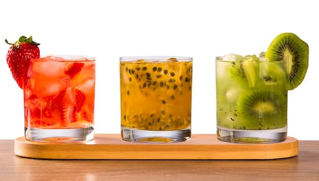 Tre bevande a base di frutto della passione, fragola e kiwi caipirinha su sfondo bianco