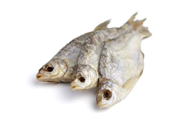 Un primo piano di tre pesci secchi isolato su bianco