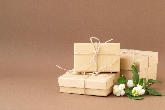 Tre scatole regalo ecologiche con snowberry su sfondo marrone