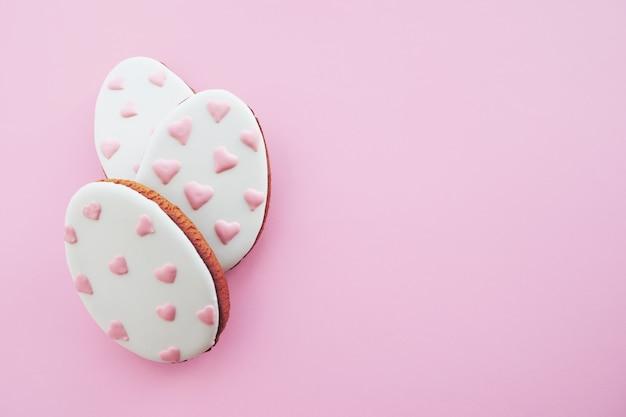 Tre biscotti a forma di uovo di pan di zenzero con cuori rosa dipinti in fila contro uno sfondo rosa. concetto di pasqua.