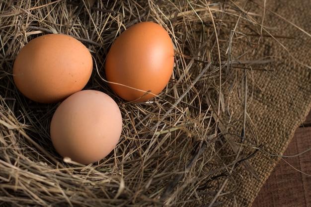 Tre uova in un nido di fieno su uno sfondo di tela su una superficie di legno, vista dall'alto, con una copia dello spazio.