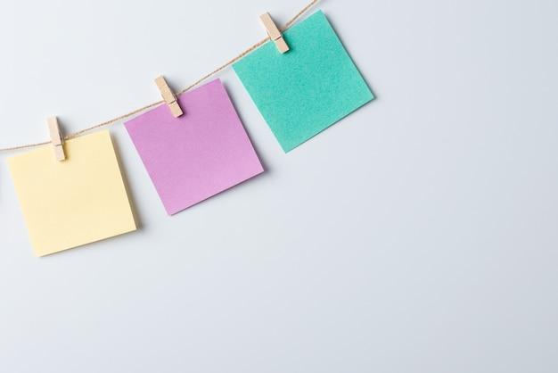 Tre carte a colori vuote sul filo contro il bordo bianco