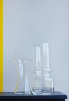 Tre vasi di vetro vuoti su sfondo giallo grigio oggetti di decorazione d'interni antichi