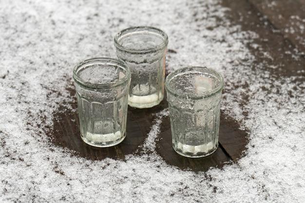 Tre bicchieri vuoti in piedi sul tavolo di legno ricoperto di neve che si scioglie all'aperto