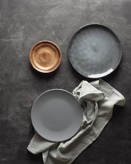 Tre piatti vuoti di diverse dimensioni su uno sfondo grigio vista dall'alto.