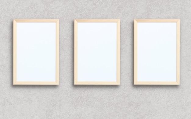 Tre cornici rettangolari vuote su una parete grigia.
