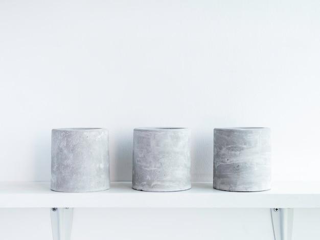 Tre vasi per piante in calcestruzzo rotondi vuoti su uno scaffale di legno bianco isolato su parete bianca con spazio per le copie. piccola fioriera in cemento fai da te per cactus, piante grasse o fiori.