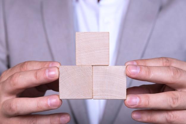 Tre cubi di legno vuoti a forma di piramide vengono messi nelle mani di un uomo d'affari. copia spazio.