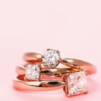 Tre anelli di fidanzamento con diamanti su uno sfondo rosa e copia spazio