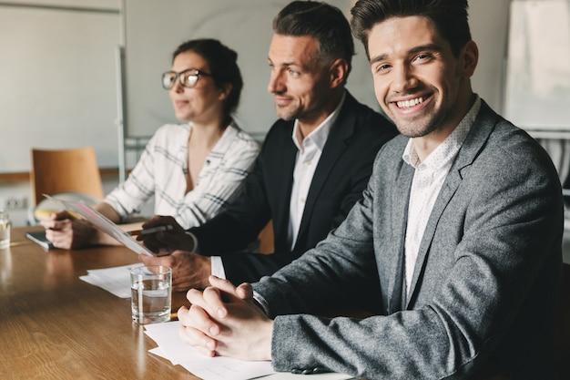 Tre direttori esecutivi o capi dirigenti in abiti formali seduti al tavolo in ufficio e intervistando nuovo personale per il lavoro di squadra: affari, carriera e concetto di collocamento