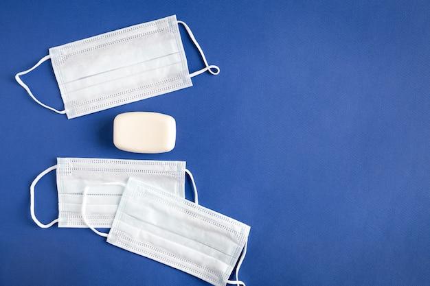 Tre maschere mediche e pezzo piatto di sapone bianco giacevano su uno sfondo di carta blu con spazio di copia